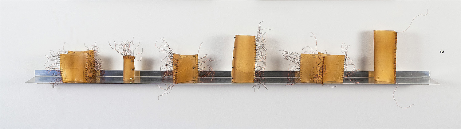Abstract scultpure titled Machine Alterations 2019 with 5 ft aluminium shelf sizes 3 – 7 inches embossed polyurethane, copper wire, brass rivets pieces